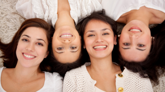 Four smiling women with heads close together